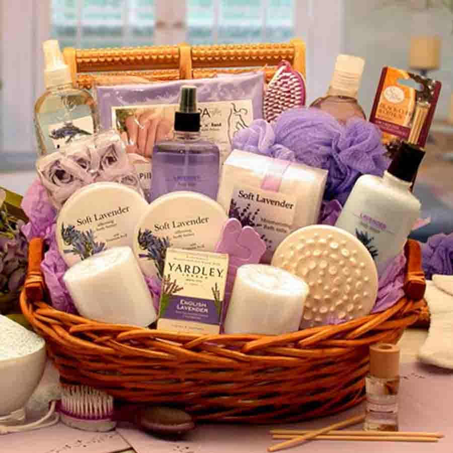 A home spa gift featuring calming Lavender products such as lavender lotion, body scrub, gel, salts, fizzies, body mist, body butter, soap, room spray, and diffuser topped off with a loofah, massagers, bath pillow, candles, and pedicure brush. Contents In #gift
