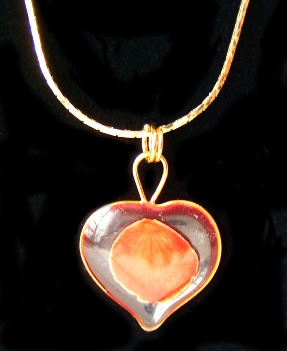 The miniature red rose petal has been preserved in a clear lacquer finish, trimmed in gold and placed in a heart shell. Our rose petal necklace is a great jewelry gift. Check out our gold rose jewelry line for more unique gift ideas. #gift
